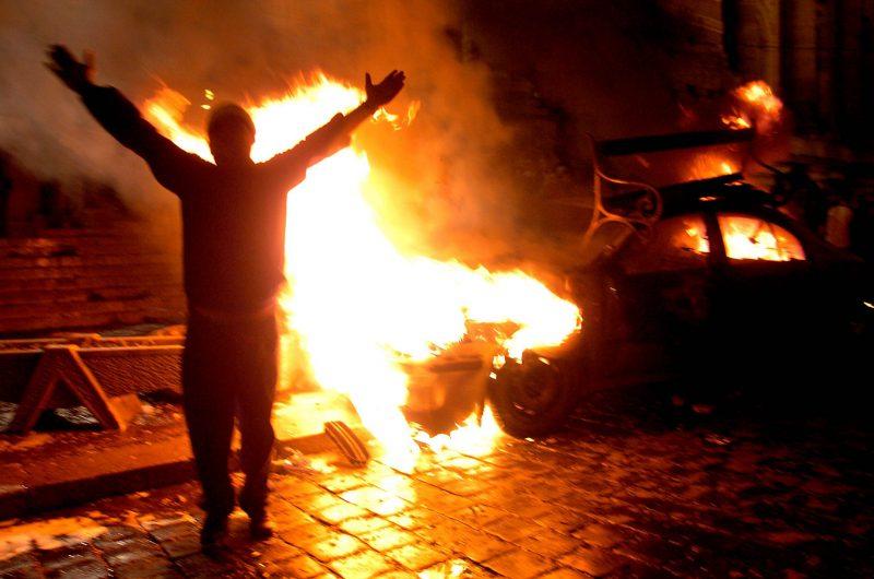 Budapest, 2006. szeptember 19. Egy tüntetõ egy égõ gépkocsi elõtt a Magyar Televízió székházánál, amikor több mint ezer fiatal rohamozta meg az MTV épületét. MTI Fotó: Kovács Tamás