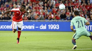 Switzerland's forward Breel Embolo (L) scores his team's first goal against Portugal's goalkeeper Rui Patricio (not pictured) during the World Cup 2018 football qualifier between Switzerland and Portugal at the St. Jakob-Park stadium in Basel on September 6, 2016. / AFP PHOTO / FABRICE COFFRINI