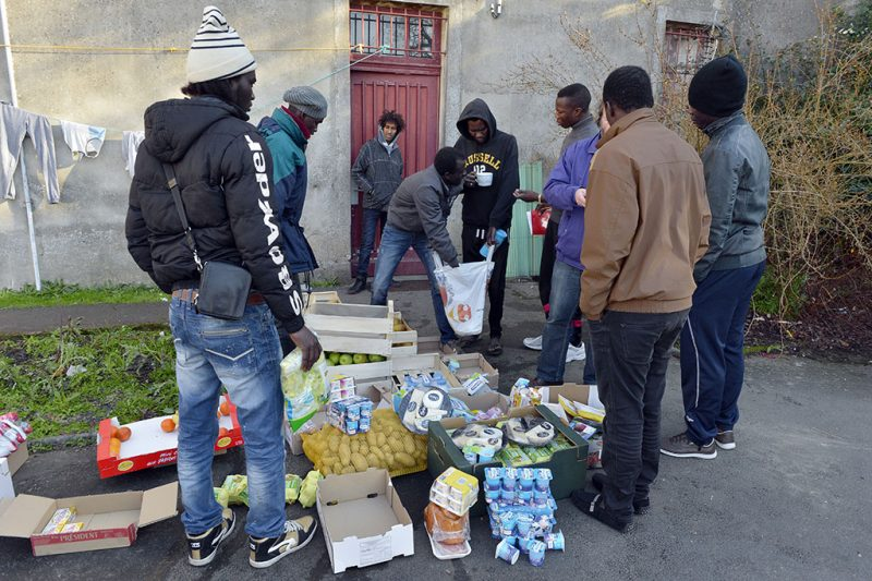Migrants seeking asylum share food in a presbytery in the Sainte-Marie-de-Doulon's parish in Nantes, western France on December 30, 2014. Some 60 migrants, expelled by police from a previous squat, took refuge in the abandonned presbytery where volunteers give them classes and some material and psychological support. AFP PHOTO/GEORGES GOBET / AFP PHOTO / GEORGES GOBET