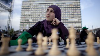 TEL AVIV, ISRAEL - OCTOBER 21: (ISRAEL OUT) An Israeli Arab chess player waits for Israeli Grandmaster Alik Gershon, during an attempt to break the Guinness world record of simultaneous chess play on October 21, 2010 in Tel Aviv, Israel. Hundreds of chess players in Israel are attempting to break the Guinness world record of simultaneous chess play. Iran currently holds the world record of 500 games played simultaneously.  (Photo by Uriel Sinai/Getty Images)