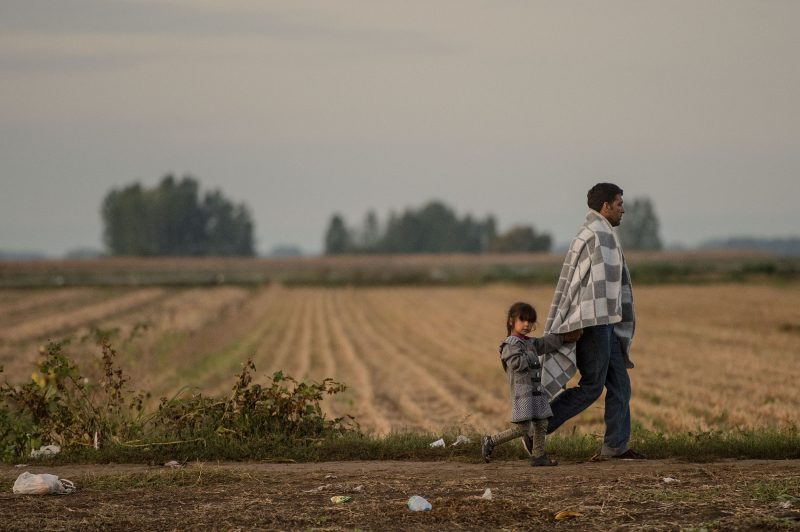 SID, SERBIA - SEPTEMBER 21:  A man and a child walk the last few kilomtres from Serbia to Croatia as more migrants continue to arrive by bus on September 21, 2015 in Sid, Serbia. Thousands of migrants have arrived in Austria over the wekend with more en-route from Hungary, Croatia and Slovenia. Politicians across the European Union are to hold meetings on the refugee crisis with EU interior ministers meeting tomorrow and EU leaders attending an extraordinary summit on Wednesday.  (Photo by David Ramos/Getty Images)
