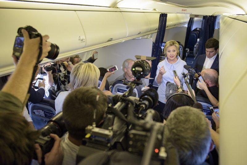Democratic presidential nominee Hillary Clinton speaks to the press onboard her plane September 5, 2016 above Iowa. / AFP PHOTO / Brendan Smialowski