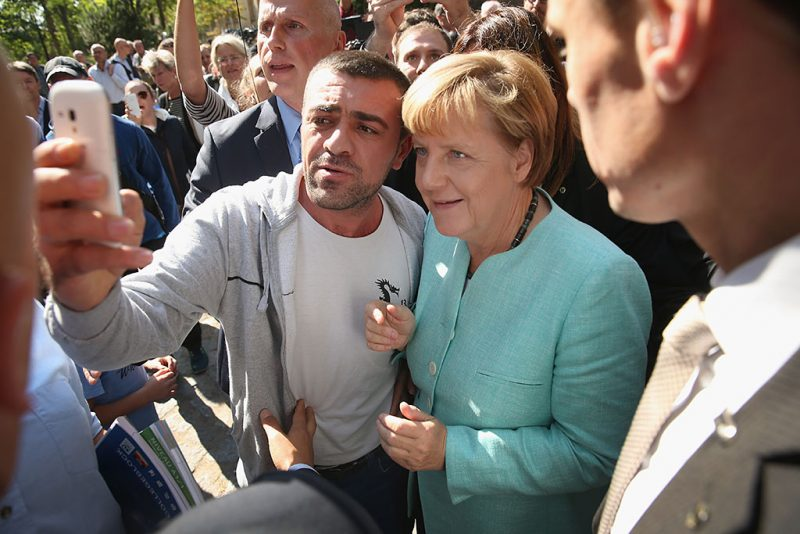 BERLIN, GERMANY - SEPTEMBER 10:  German Chancellor Angela Merkel pauses for a selfie with a migrant after she visited the AWO Refugium Askanierring shelter for migrants on September 10, 2015 in Berlin, Germany. Merkel visited several facilities for migrants today, including an application center for asylum-seekers, a school with welcome classes for migrant children and a migrant shelter. Thousands of migrants are currently arriving in Germany every day, most of them via the Balkans and Austria. Germany is expecting to receive 800,000 asylum applicants this year.  (Photo by Sean Gallup/Getty Images)