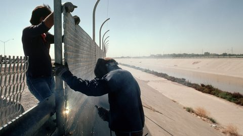 """Two workers weld part of the galvanized steel fence being built along the length of the border between the United States and Mexico in 1979. The fence, intended to keep illegal aliens from crossing into the US, is known as the """"Tortilla Curtain."""" (Photo by © Stephanie Maze/CORBIS/Corbis via Getty Images)"""