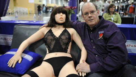 """Engineer-inventor Douglas Hines poses with his company's """"True Companion"""" sex robot, Roxxxy, at the TrueCompanion.com booth at the AVN Adult Entertainment Expo in Las Vegas, Nevada, January 9, 2010.  In what is billed as a world first, a life-size robotic girlfriend complete with artificial intelligence and flesh-like synthetic skin was introduced to adoring fans at the AVN Adult Entertainment Expo.    AFP PHOTO / Robyn Beck"""