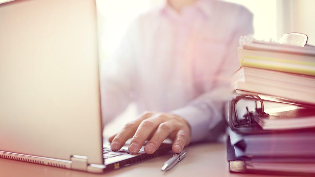 Businessman or designer using laptop computer at desk in office