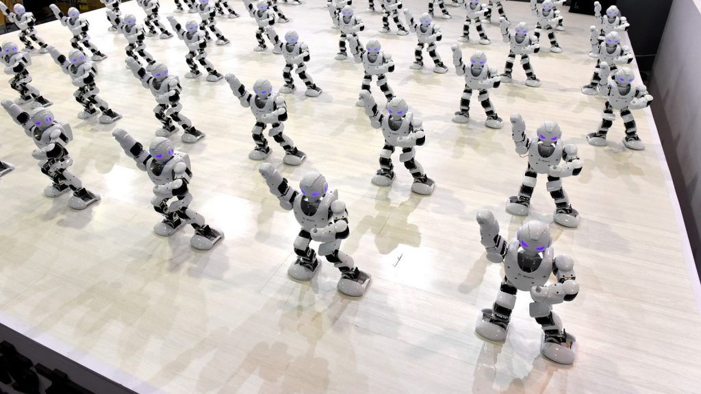 """JINAN, CHINA - AUGUST 25:  More than 50 robots dance during the opening ceremony of the sixth Shandong Cultural Industries Fair (SDCIF) at Jinan International Convention & Exhibition Center on August 25, 2016 in Jinan, Shandong Province of China.The 50 robots are named """"Alpha"""" and are connected to cellphones instructing them to perform different actions according to various musical sounds.  (Photo by VCG/VCG via Getty Images)"""