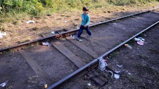 """Following his family, a migrant boy walks alone between the railroad tracks near Roszke village of the Hungarian-Serbian border on August 27, 2015. As Europe struggles with its worst migrant crisis since World War II, Hungary has become, like Italy and Greece, a """"front line"""" state. So far this year, police say around 141,500 migrants have been intercepted crossing into Hungary, mostly from neighboring Serbia.   AFP PHOTO / ATTILA KISBENEDEK / AFP PHOTO / ATTILA KISBENEDEK"""