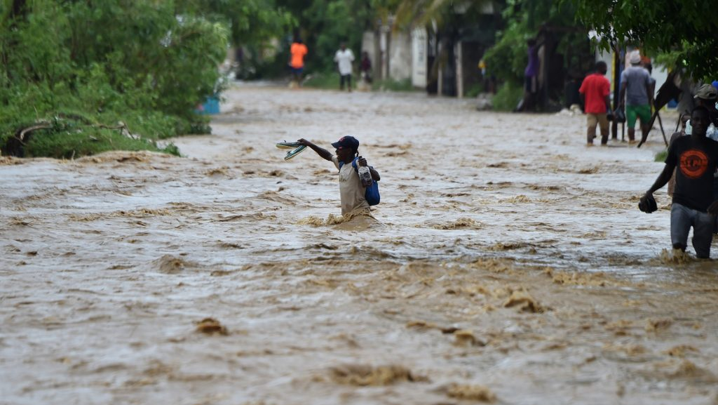 People try to cross the overflowing La Rouyonne river in the commune of Leogane, south of Port-au-Prince, October 5, 2016.  Haiti and the eastern tip of Cuba -- blasted by Matthew on October 4, 2016 -- began the messy and probably grim task of assessing the storm's toll. Matthew hit them as a Category Four hurricane but has since been downgraded to three, on a scale of five, by the US National Hurricane Center.  / AFP PHOTO / HECTOR RETAMAL