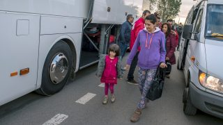 """A Kurdish Iraqi family prepares to board a bus to leave the """"Jungle"""" migrant camp in Calais on October 12, 2016. French authorities are preparing to raze the Calais """"Jungle"""" camp and move thousands of migrants to shelters nationwide. / AFP PHOTO / PHILIPPE HUGUEN"""