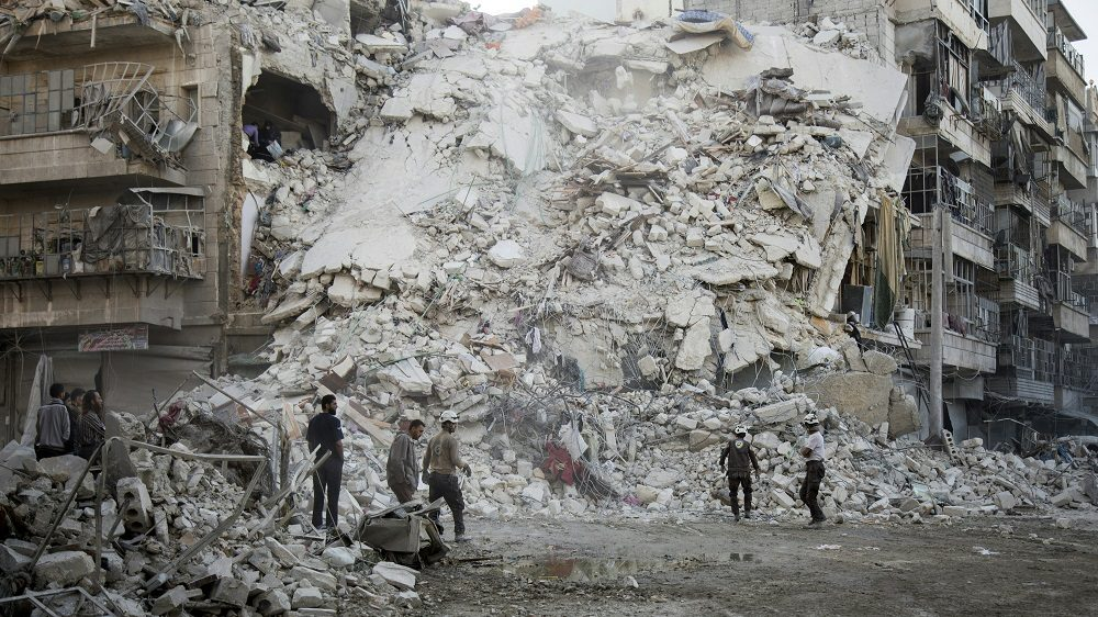 Members of the Syrian Civil Defence, known as the White Helmets, search for victims amid the rubble of a destroyed building following reported air strikes in the rebel-held Qatarji neighbourhood of the northern city of Aleppo, on October 17, 2016.  Dozens of civilians were killed as air strikes hammered rebel-held parts of Aleppo early morning, despite Western warnings of potential sanctions against Syria and Russia over attacks on the city. Both Russian and Syrian warplanes are carrying out air strikes over Aleppo in support of a major offensive by regime forces to capture rebel-held parts of the northern city.  / AFP PHOTO / KARAM AL-MASRI