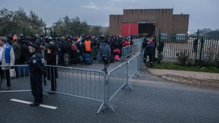 FRANCE, Calais: Police watch over migrants from Calais Jungle who wait in line to get on buses as France begins clearing the migrant camp in the port city of Calais on Sunday, October 23, 2016. The refugee camp has been a makeshift home for thousands of refugees who attempt to reach Britain. The evacuated refugees are sent to different refugee centers across France or back to their home countries. The UK has also started to accept some of the unaccompanied children from the camp. - Kamila Stepien