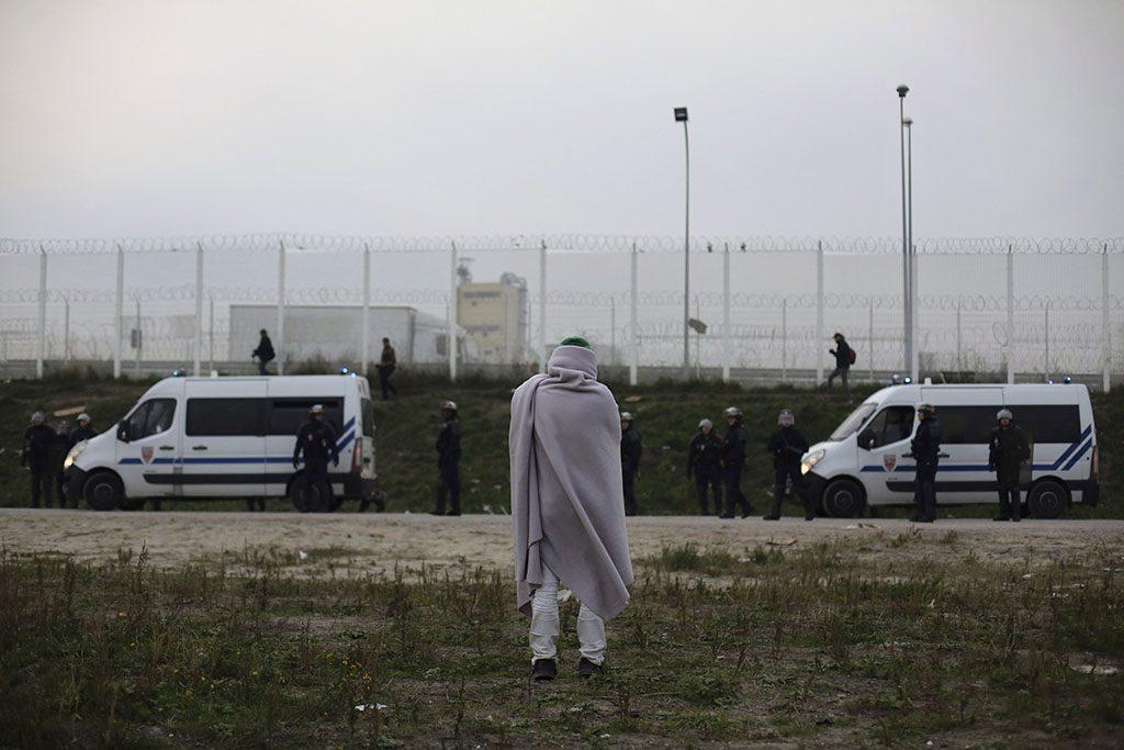 Calais, 2016.október 24.Áttelepítésre váró illegális bevándorló rendőrségi járművek közelében a nyugat-franciaországi Calais-nál kialakult, Dzsungel néven ismertté vált migránstáborban 2016. október 23-án, a táborbontás kezdete előtti napon. A telepen elszállásolt mintegy 6400, elsősorban szudáni, eritreai és afgán állampolgárt buszokkal szállítják át az ország különböző pontjain kialakított 287 átmeneti befogadóközpontba. A kiürítés a tervek szerint egy hét alatt lezajlik, az első napon 2400 embernek kell elhagynia a tábort. (MTI/AP/Etienne Laurent)