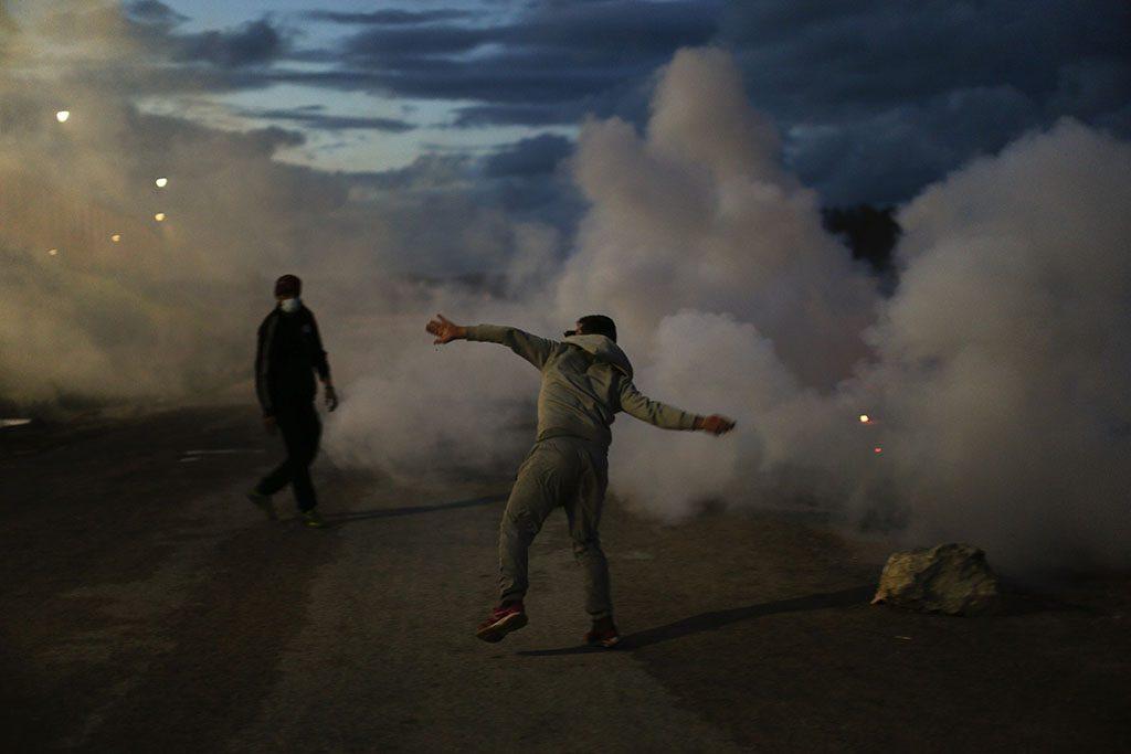 Calais, 2016. október 23.Egy tüntető kővel dobálja a francia rendőröket a Franciaországból Nagy-Britanniába átjutni szándékozó több ezer illegális bevándorló táborának lakói és a rendfenntartók közötti összecsapásban a franciaországi Calais-ban 2016. október 22-én. A francia hatóságok szerint október 24-én megkezdik a Dzsungelnek nevezett tábor felszámolását, ami körülbelül egy hétig fog tartani. (MTI/AP/Emilio Morenatti)