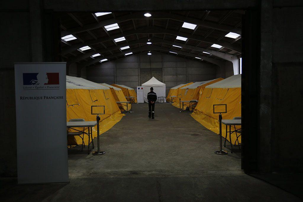 Calais, 2016.október 24.Kiürített sátrakkal teli csarnokban áll a biztonsági erők egyik tagja a nyugat-franciaországi Calais-nál kialakult, Dzsungel néven ismertté vált migránstáborban 2016. október 24-re virradóra, a táborbontás kezdetén. A telepen elszállásolt mintegy 6400, elsősorban szudáni, eritreai és afgán állampolgárt buszokkal szállítják át az ország különböző pontjain kialakított 287 átmeneti befogadóközpontba. A kiürítés a tervek szerint egy hét alatt lezajlik, az első napon 2400 embernek kell elhagynia a tábort. (MTI/AP/Emilio Morenatti)