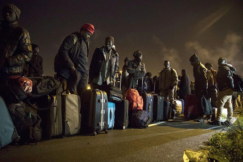 Calais, 2016.október 24.Csomagjaik mellett várakozó illegális bevándorlók, mielőtt elhagyják a nyugat-franciaországi Calais-nál kialakult, Dzsungel néven ismertté vált migránstábort 2016. október 24-re virradóra. A táborban elszállásolt mintegy 6400, elsősorban szudáni, eritreai és afgán állampolgárt buszokkal szállítják át az ország különböző pontjain kialakított 287 átmeneti befogadóközpontba. A kiürítés a tervek szerint egy hét alatt lezajlik, az első napon 2400 embernek kell elhagynia a telepet. (MTI/EPA/Etienne Laurent)