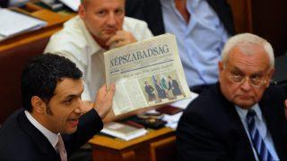 Budapest, 2010. július 22. Lázár János, a Fidesz parlamenti frakcióvezetõje (b) a szocialista frakció tagjainak a korabeli újság címlapját mutatja, így demonstrálva, mit ígértek és mi lett a valóság. Az Országgyûlés nyári rendkívüli ülésszakának utolsó ülésén a parlament új házelnököt, alkotmánybírákat is választ, és dönt a kormány 29 pontos gazdasági akciótervéhez kapcsolódó pénzügyi törvénycsomagról.  MTI Fotó: Koszticsák Szilárd
