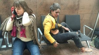 BRUSSELS, BELGIUM - MARCH 22:   Flight attendant Nidhi Chaphekar (R) reacts in the moments following a suicide bombing at Brussels Zaventem airport on March 22, 2016 in Brussels, Belgium. Georgian journalist Ketevan Kardava, special correspondent for the Georgian Public Broadcaster, was travelling to Geneva when the attack took place, she was knocked to the floor and began to take photographs in the moments that followed. At least 31 people were killed and more than 260 injured in a twin suicide blast at Zaventem Airport and a further bomb attack at Maelbeek Metro Station. Two brothers are thought to have carried out the attacks and a manhunt is underway for a third suspect.   (Photo by Ketevan Kardava/Getty Images)