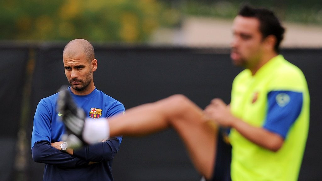 Barcelona FC head coach Josep Guardiola (L) looks on as midfielder Xavi Hernandez streches during a training session at UCLA in Los Angeles on July 30, 2009. Barcelona will face the Los Angeles Galaxy on August 1 in Pasadena, California.  AFP PHOTO / GABRIEL BOUYS / AFP PHOTO / GABRIEL BOUYS