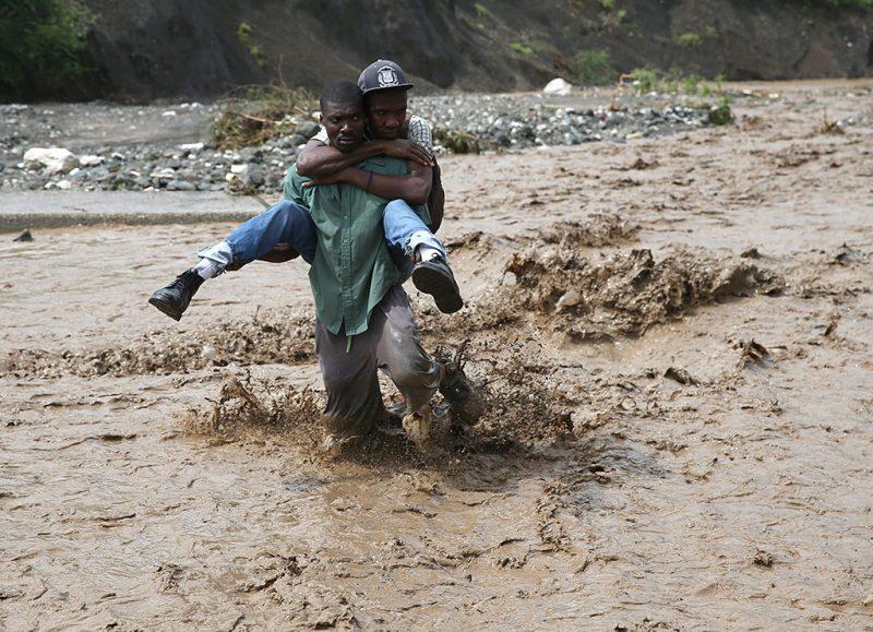 Petit Goave, 2016. október 6.Helyiek gázolnak a vízben a Matthew névre keresztelt trópusi vihar miatt elöntött utcák egyikén a Haiti délnyugati részén fekvő Petit Goavéban 2016. október 5-én. Eddig legkevesebb 26 halálos áldozatot követelt és súlyos károkat okozott a Karib-tengeri térségben a hurrikán, amely helyi idő szerint október 6-án este éri el Florida keleti partjait. (MTI/EPA/Orlando Barria)