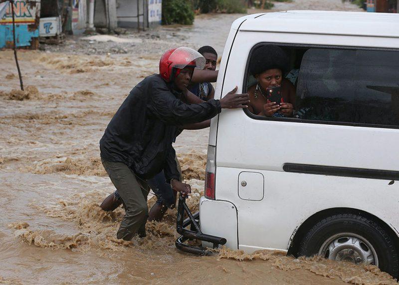 Léogane, 2016. október 6.Két férfi tol egy kisbuszt a vízben a Matthew névre keresztelt trópusi vihar miatt elöntött utcák egyikén a Haiti délnyugati részén fekvő Léoganéban 2016. október 5-én. Eddig legkevesebb 26 halálos áldozatot követelt és súlyos károkat okozott a Karib-tengeri térségben a hurrikán, amely helyi idő szerint október 6-án este éri el Florida keleti partjait. (MTI/EPA/Orlando Barria)