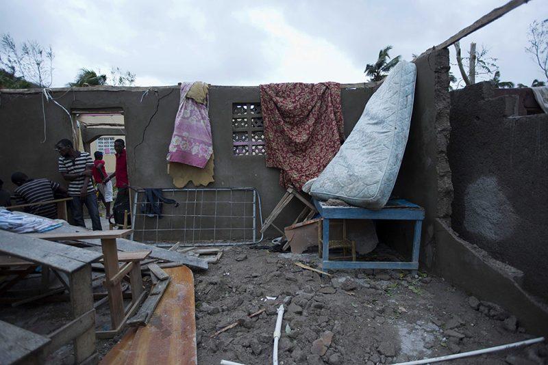 Saint-Louis, 2016. október 6.Helyiek a Matthew névre keresztelt trópusi vihar által megrongált lakóházak egyikében a Haitiban fekvő Saint-Louisban 2016. október 5-én. Eddig legkevesebb 26 halálos áldozatot követelt és súlyos károkat okozott a Karib-tengeri térségben a hurrikán, amely helyi idő szerint október 6-án este éri el Florida keleti partjait. (MTI/AP/Dieu Nalio Chery)