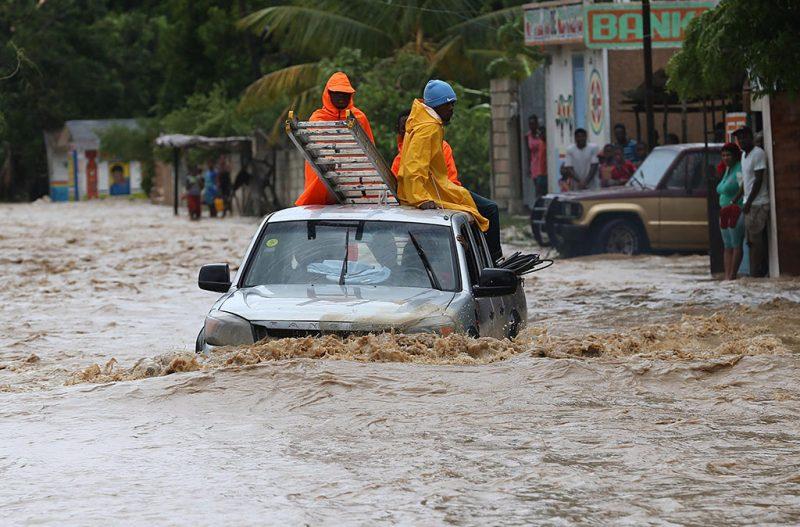 Léogane, 2016. október 6.Helyiek gázolnak a vízben a Matthew névre keresztelt trópusi vihar miatt elöntött utcák egyikén a Haiti délnyugati részén fekvő Léoganéban 2016. október 5-én. Eddig legkevesebb 26 halálos áldozatot követelt és súlyos károkat okozott a Karib-tengeri térségben a hurrikán, amely helyi idő szerint október 6-án este éri el Florida keleti partjait. (MTI/EPA/Orlando Barria)