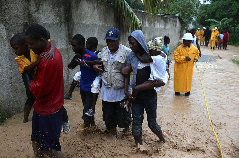 Fonds Parisiens, 2016. október 5.Helyiek gázolnak a vízben a Matthew névre keresztelt trópusi vihar miatt elöntött utcák egyikén a Haiti nyugati részén fekvő Fonds Parisiens-ben 2016. október 4-én. (MTI/EPA/Orlando Barria)