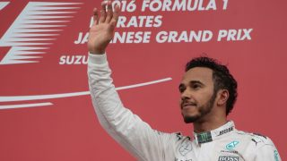 Third-placed Mercedes AMG Petronas F1 Team's British driver Lewis Hamilton waves his hand as he arrives at the podium after the Formula One Japanese Grand Prix at the Suzuka Circuit on October 9, 2016.  / AFP PHOTO / YUYA SHINO