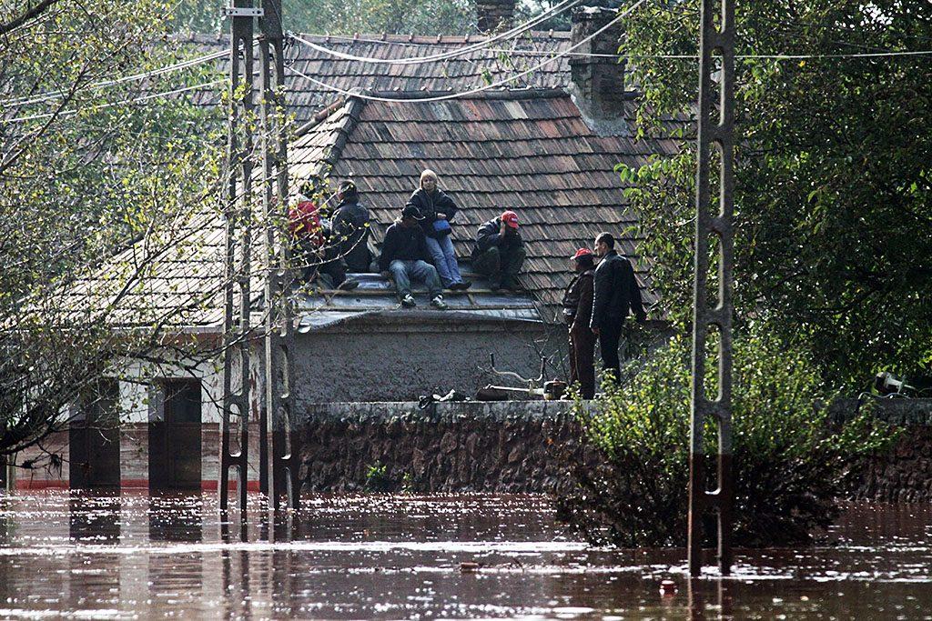 Devecser, 2010. október 4.Háztetőn ülő emberek várnak kimentésükre Devecseren, miután Ajkán átszakadt az iszaptároló gátja, és az erősen mérgező iszap elérte a települést. A víz rendkívül erős, 13 pH értékű lúgot tartalmaz.MTI Fotó: Nagy Lajos