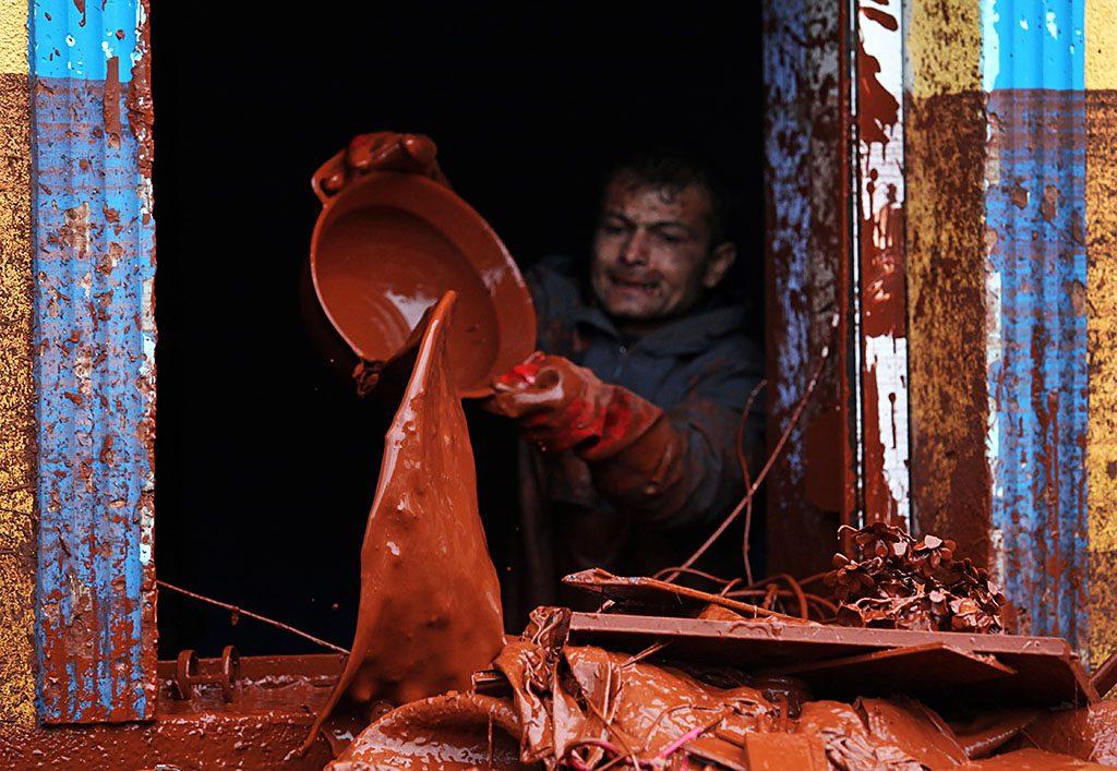 Devecser, 2010. október 6.Egy férfi vörösiszapot önt ki egy ház ablakán Devecseren. A Magyar Alumínium Termelő és Kereskedelmi Zrt. (MAL Zrt.) Ajka melletti tározójából 2010. október 4-én mintegy egymillió köbméternyi mérgező, maró hatású vörösiszap ömlött ki gátszakadás miatt. A katasztrófa három települést - Devecser, Kolontár, Somlóvásárhely – érint, közel 40 négyzetkilométeres terület lakossága és élővilága van veszélyben.MTI Fotó: Mohai Balázs
