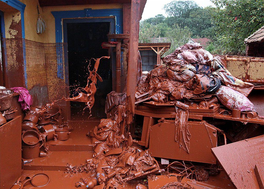 Devecser, 2010. október 6.Vörösiszappal borított, elszállításra váró, kidobott lakberendezési és haszálati tárgyak hevernek egy devecseri ház előtt. A Magyar Alumínium Termelő és Kereskedelmi Zrt. (MAL Zrt.) Ajka melletti tározójából 2010. október 4-én mintegy egymillió köbméternyi mérgező, maró hatású vörösiszap ömlött ki gátszakadás miatt. A katasztrófa három települést - Devecser, Kolontár, Somlóvásárhely – érint, közel 40 négyzetkilométeres terület lakossága és élővilága van veszélyben.MTI Fotó: Mohai Balázs