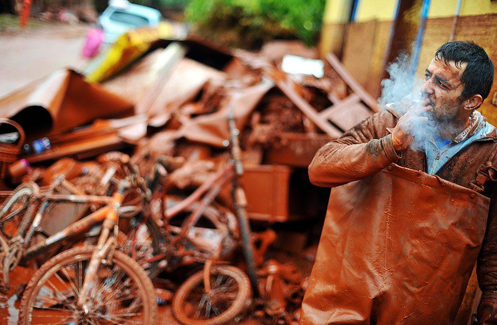 Devecser, 2010. október 6.Egy férfi cigarettázik, miközben tönkrement ingóságait hordja egyrakásra Devecseren, miután a Magyar Alumínium Termelő és Kereskedelmi Zrt. (MAL Zrt.) Ajka melletti tározójából 2010. október 4-én mintegy egymillió köbméternyi mérgező, maró hatású vörösiszap ömlött ki gátszakadás miatt. A katasztrófa három települést - Devecser, Kolontár, Somlóvásárhely – érint, közel 40 négyzetkilométeres terület lakossága és élővilága van veszélyben.MTI Fotó: Kovács Tamás