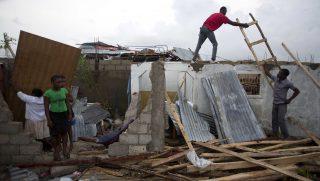 Les Cayes, 2016. október 6. Férfiak megrongálódott házuk tetõszerkezetét próbálják megjavítani Les Cayesben, Haitin 2016. október 6-án, a Matthew névû trópusi vihar elvonulása után. Az elmúlt évtized egyik legerõsebb hurrikánjaként számon tartott Matthew heves esõzésekkel és óránkénti 230 kilométeres széllökésekkel söpört végig Haitin, ahol a halálos áldozatok száma elérte a 136 fõt. (MTI/AP/Dieu Nalio Chery)
