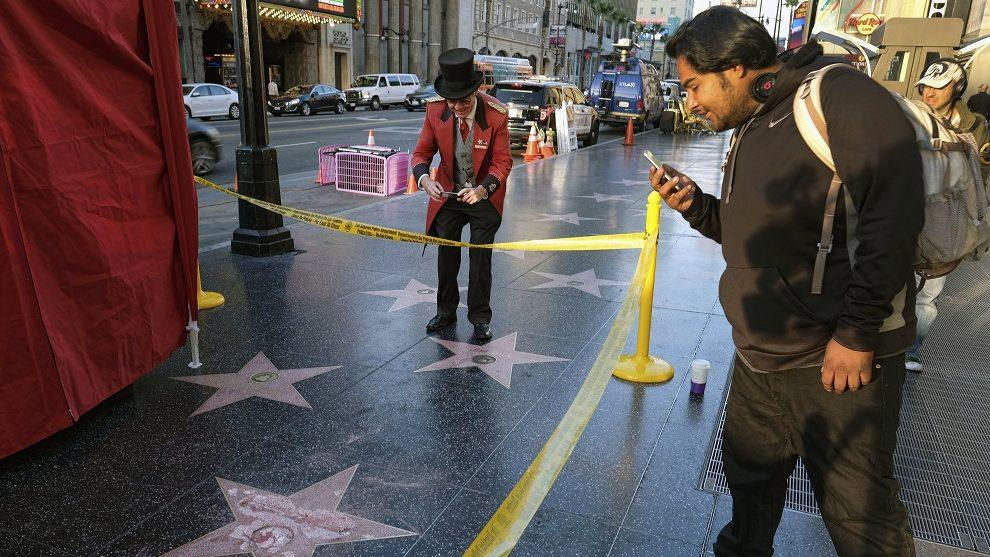 Los Angeles, 2016. október 26. Egy férfi felvételt készít Donald Trump republikánus párti elnökjelölt ismeretlen tettesek által megrongált csillagáról a Hollywoodi hírességek sétányán, Los Angelesben 2016. október 26-án. (MTI/AP/Richard Vogel)