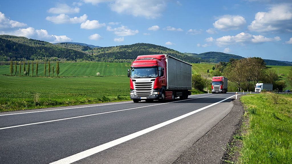 Three trucks driving on asphalt road between green fields in the countryside. Wooded mountains in the background. Sunny day with blue skies and white clouds.