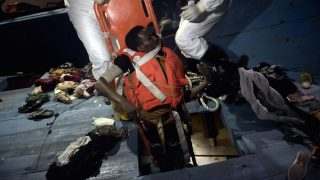 EDITORS NOTE: Graphic content / Members of Proactiva Open Arms NGO evacuate a dead body on a stretcher from the third level of a wooden vessel during a rescuing operation in the Mediterranean Sea, some 12 nautical miles north of Libya, on October 4, 2016. At least 1,800 migrants were rescued off the Libyan coast, the Italian coastguard announced, adding that similar operations were underway around 15 other overloaded vessels. / AFP PHOTO / ARIS MESSINIS