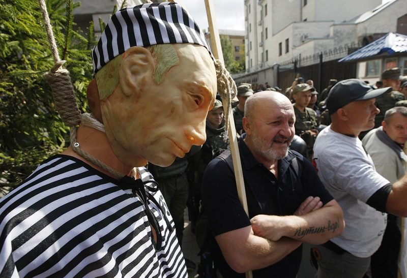 An activist stands with an effigy of Russian President Vladimir Putin as Ukrainian servicemen stand guard, during a protest near the Russian embassy in Kiev, Ukraine, 18 September 2016. A group of Ukrainian activists gathered in front of the Russian embassy to protest against the Russian parliamentary elections in a polling station in the Russian embassy.  (Photo by STR/NurPhoto)