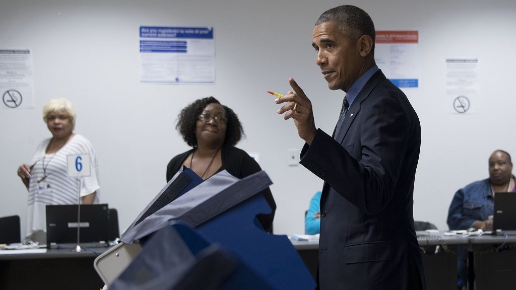 Poll workers look on as US President Barack Obama (C) gestures towards the press as he votes early at the Cook County Office Building in Chicago, Illinois, October 7, 2016. Obama cast an early ballot on Friday, highlighting a Democratic drive to get voters to the polls even before November 8. During an unannounced visit, Obama stood before a voting machine at the Chicago Board of Elections office, punched in his choice and smirked when asked who he had voted for.  / AFP PHOTO / JIM WATSON