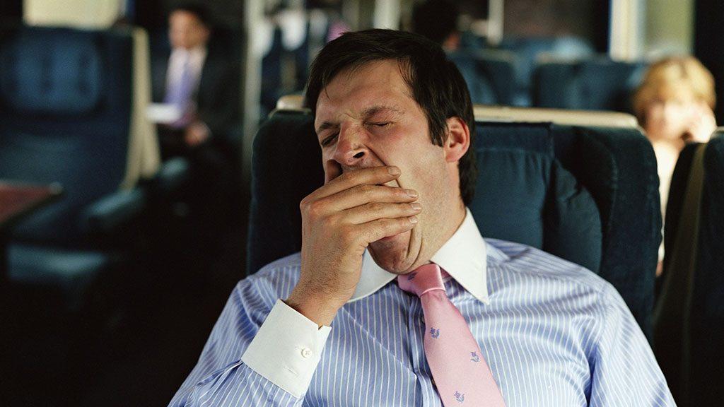 Businessman yawning on train (focus on man)