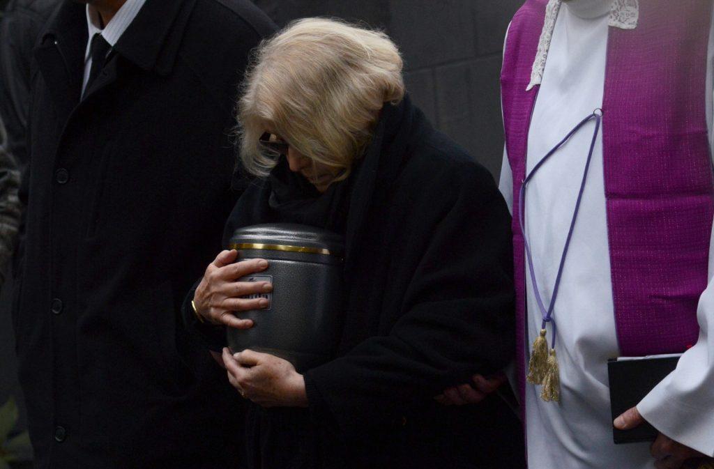 Krystyna Zachwatowicz (C), widow of late Polish filmmaker Andrzej Wajda carries the ashes urn during the funeral ceremony in Salwator cemetery in Krakow on October 19, 2016.   Wajda died on October 9 aged 90.  / AFP PHOTO / Bartosz Siedlik