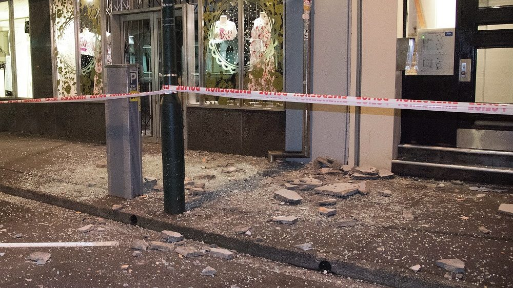 Debris from buildings are seen on a sidewalk past a cordon line in Wellington early on November 14, 2016 following an earthquake centred some 90 kilometres (57 miles) north of New Zealand's South Island city of Christchurch.  A powerful 7.8 magnitude earthquake rocked New Zealand early November 14, the US Geological Survey said, prompting a tsunami warning and knocking out power and phone services in many parts of the country.  / AFP PHOTO / Marty Melville