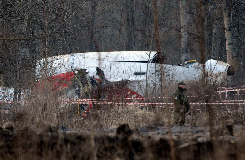 (FILES) This file photo taken on April 11, 2010 shows a Russian Interior Ministry soldier standing guard near the wreckage of a Polish government Tupolev Tu-154 aircraft which crashed on April 10, 2010 near Smolensk airport. Justice officials in Poland are exhuming the remains of dozens of people who died in a 2010 presidential jet crash in Russia but not all of the victims' families agree. PiS leader Jaroslaw Kaczynski's twin brother, then president Lech Kaczynski, was among the 96 people -- most of them senior Polish state officials -- who died when the plane went down in Smolensk, western Russia, in April 2010. / AFP PHOTO / NATALIA KOLESNIKOVA