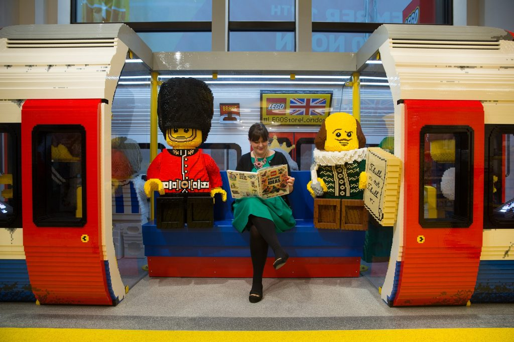 An employee poses for a picture sitting inside a London Underground tube train carriage made with LEGO pieces before the official opening of  the new LEGO store in Leicester Square, central London in November 17, 2016.  Billed as the world's largest LEGO store by the company, the new UK flagship store was officially opened on November 17 in Leicester Square. / AFP PHOTO / Daniel LEAL-OLIVAS