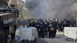 Bulgarian riot police stand near garbarge bins during clashes in the migrants reception centre in the town of Harmanli on November 24, 2016.  About 1,500 migrants started a riot on November 24 in Bulgaria's largest refugee camp, setting fires and hurling stones at police, local police spokewoman Nina Nikolova said. / AFP PHOTO / STRINGER