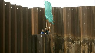 Palestinian children wave Hamas flags as they demonstrate on the metal fence that was brought down by militants in January in the bordertown of Rafah between Egypt and the Gaza Strip on April 25, 2008. Egyptian and Hamas forces resealed the frontier on February 4. Thousands of Hamas supporters demonstrated in Gaza today to demand that Israel lift its crippling blockade of the impoverished Palestinian territory. The protesters massed in the north and the south of the narrow strip of land near border crossings into Israel and Egypt. AFP PHOTO/SAID KHATIB / AFP PHOTO / SAID KHATIB