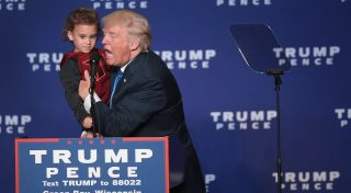 GREEN BAY, WI - OCTOBER 17: Republican presidential nominee Donald Trump holds a child while speaking at a campaign rally at the KI Convention Center on October 17, 2016 in Green Bay, Wisconsin. Trump will square off with democratic rival Hillary Clinton for a final debate before the election on October 19 in Las Vegas.   Scott Olson/Getty Images/AFP