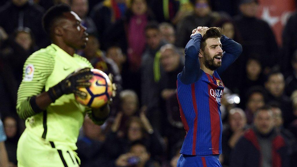 Barcelona's defender Gerard Pique (R) gestures past Malaga's Cameroonian goalkeeper Carlos Kameni during the Spanish league football match FC Barcelona vs Malaga CF at the Camp Nou stadium in Barcelona, on November 19, 2016. / AFP PHOTO / LLUIS GENE