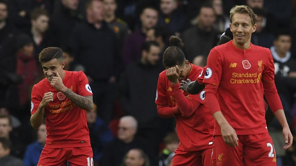 Liverpool's Brazilian midfielder Philippe Coutinho (L) dances as he celebrates scoring his team's second goal with Liverpool's Brazilian midfielder Roberto Firmino (C) during the English Premier League football match between Liverpool and Watford at Anfield in Liverpool, north west England on November 6, 2016. / AFP PHOTO / PAUL ELLIS / RESTRICTED TO EDITORIAL USE. No use with unauthorized audio, video, data, fixture lists, club/league logos or 'live' services. Online in-match use limited to 75 images, no video emulation. No use in betting, games or single club/league/player publications.  /