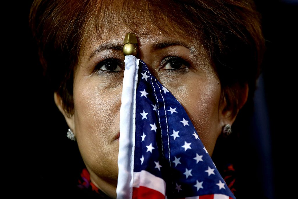 NEW YORK, NY - NOVEMBER 09:  A woman holds an American flag to her face as she watches the voting results at Democratic presidential nominee former Secretary of State Hillary Clinton's election night event at the Jacob K. Javits Convention Center November 8, 2016 in New York City. Clinton is running against Republican nominee, Donald J. Trump to be the 45th President of the United States.  (Photo by Win McNamee/Getty Images)
